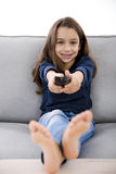 Girl holding a TV remote Stock Photo