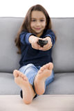 Girl holding a TV remote Royalty Free Stock Photos