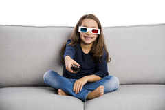 Girl holding a TV remote Royalty Free Stock Image