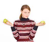 Girl holding two apples decides which to choose Royalty Free Stock Images