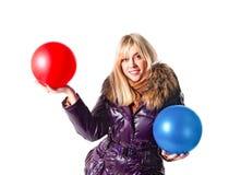 Girl holding two balls Royalty Free Stock Photos