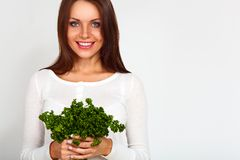 Girl holding two bunches of parsley near the face Stock Photos
