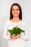 Girl holding two bunches of parsley near the face Royalty Free Stock Photos