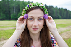 Girl holding two field flowers. Freckled girl holding two field flowers at eye level Royalty Free Stock Photo