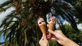 Girl holding two ice creams with one hand. On palm trees background stock video