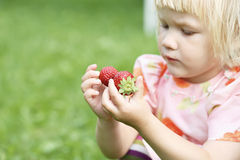Girl holding two strawberries. Stock Photography