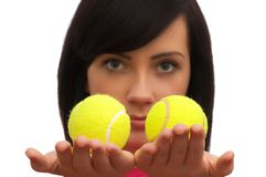 Girl holding two tennis balls. On white Stock Image