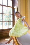 Girl (10-12) holding up dress by window, smiling, portrait Royalty Free Stock Photo