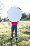 Girl Holding up Light Diffuser With Both Hands Royalty Free Stock Photos