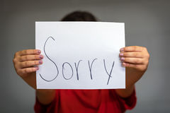 Girl Holding Up Sorry. A girl holding up a paper saying sorry Stock Photos