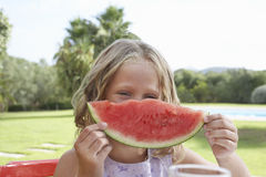 Girl Holding Up Watermelon Slice In Front Of Face Stock Image
