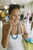 Girl Holding Using Cell Phone in clothing store Stock Photography