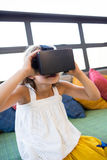 Girl holding virtual reality headset while sitting in library Stock Photo