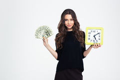 Girl holding wall clock and bills of dollars. Portrait of a happy young girl holding wall clock and bills of dollars Royalty Free Stock Photos