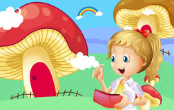 A girl holding a wallet near the giant mushroom houses Royalty Free Stock Images