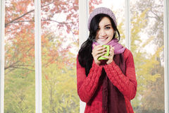 Girl holding warm drink in autumn Stock Images