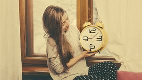 The girl is holding a watch. The nice girl is holding a big watch. The alarm clock shows nine hours and ten minutes Stock Image