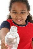 Girl holding water bottle. Little girl offering a bottle of water Stock Images