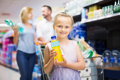 Girl holding water bottle. Cheerful girl holding water bottle in supermarket Stock Photography