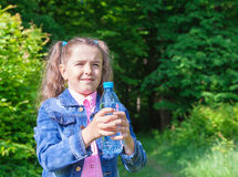 Girl holding a water bottle. Girl in a denim jacket holding a water bottle outdoor closeup Royalty Free Stock Photos