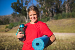 Girl holding a water bottle and exercise mat in the boot camp. Portrait of girl holding a water bottle and exercise mat in the boot camp Royalty Free Stock Image