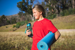 Girl holding a water bottle and exercise mat in the boot camp. On a sunny day Stock Photos