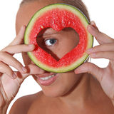 Girl holding watermelon. Cut in heart shape in front of eyes Royalty Free Stock Images