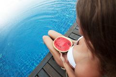 Girl with watermelon in pool. Girl holding watermelon sitting by the blue swimmin pool royalty free stock photo