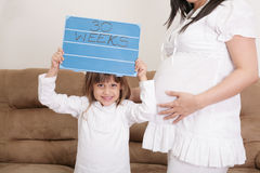 Girl holding a 30 weeks sign to her expectant mother.  royalty free stock image