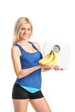 Girl holding a weight scale and bananas Royalty Free Stock Images