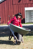 Girl holding wheelbarrow. At a farm royalty free stock photos