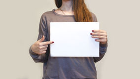 Girl holding white A4 blank paper horizontally. Leaflet presentation. Pamphlet hold hands. Woman show clear offset paper. Sheet t. Emplate. Booklet design sheet royalty free stock image