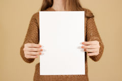 Girl holding white A4 blank paper vertically. Leaflet presentation. Pamphlet hold hands. Woman show clear offset paper. Sheet. Template. Booklet design sheet royalty free stock photo