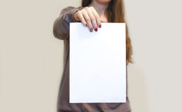 Girl holding white A4 blank paper vertically. Leaflet presentation. Pamphlet hold hands. Woman show clear offset paper. Sheet. Template. Booklet design sheet royalty free stock photography