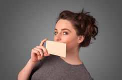 Girl holding white card at front of her lips with copy spac. Cute girl holding white card at front of her lips with copy space on gradient background Royalty Free Stock Photos