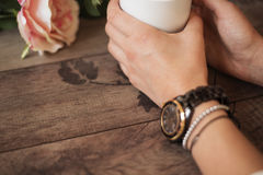 Girl is holding white cup in hands. White mug for woman, gift. Female hands with watch and bracelets holding hot cup of coffee Stock Image