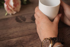 Girl is holding white cup in hands. White mug for woman, gift. Female hands with watch and bracelets holding hot cup of coffee Stock Images