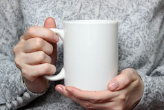 Girl is holding white cup in hands. White mug in woman's hands. Mockup for designs Stock Photo