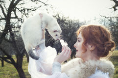 Girl holding a white ferret Stock Images
