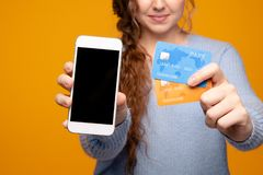 Girl holding white iphone and two gredit cards stock image