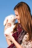 Girl holding a white little rabbit Stock Photos