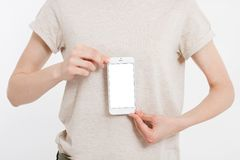 Girl holding white phone. Cellular isolated on white clipping path inside. Top view.Mock up.Copy space.Template.Blank. Girl holding white phone. Cellular royalty free stock photography