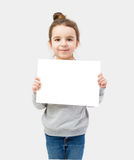 Girl holding a white plate on a gray background Royalty Free Stock Photo