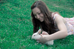 Girl holding a white rabbit. Girl in a pink dress holding a white rabbit on a grassy background Stock Photo