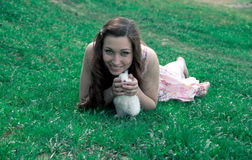 Girl holding a white rabbit. Girl in a pink dress holding a white rabbit on a grassy background Stock Photos