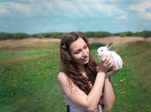 Girl holding a white rabbit. Girl in a pink dress holding a white rabbit on nature background Stock Images