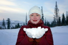 Girl holding the white snow on the hands. Stock Photo