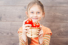 Girl holding wicker basket with red tomatoes Royalty Free Stock Photography