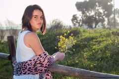 Girl holding wild flower outdoors. Looking back royalty free stock photo