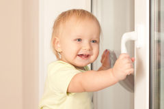 Girl holding window knob Royalty Free Stock Images